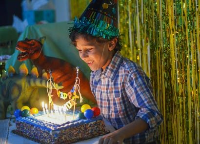 Excited Young Boy In A Party Hat About To Blow Out Candles On Birthday Cake